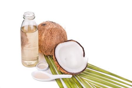 coco: Prensado en frío de aceite de coco virgen extra en botellas de coco con frutas en el fondo blanco