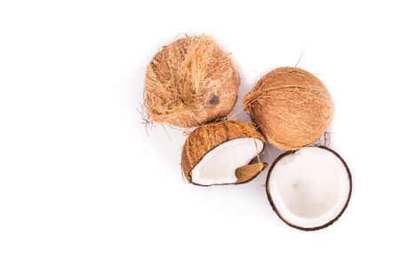 copra: Overhead view of old brown organic coconut fruits with one broken into half on white background