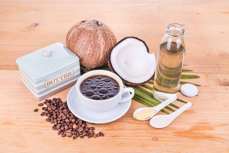 Bulletproof koffie met koudgeperste extra vierge kokosolie en gras gevoed organische boter op houten tafel, een deel van het ketogeen dieet Stockfoto