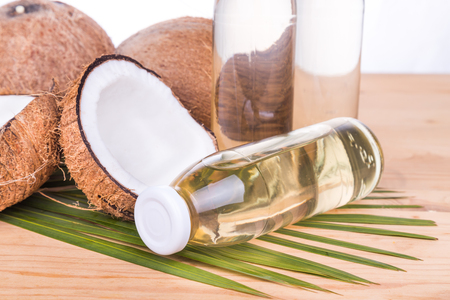 extra virgin: Closed up on old pressed extra virgin coconut oil in bottles with coconut fruits as background Stock Photo