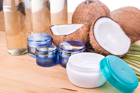 extra virgin: Closeup on cold pressed extra virgin coconut oil in bottles and coconut processed oil in skincare jars with coconut fruits as background