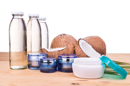 aceite de coco: Prensado en frío de aceite de coco virgen extra en botellas y aceite de coco procesada en frascos de cuidado de la piel de coco con frutas como fondo