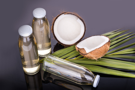 extra virgin: Cold pressed extra virgin coconut oil in bottles with coconut fruits as background