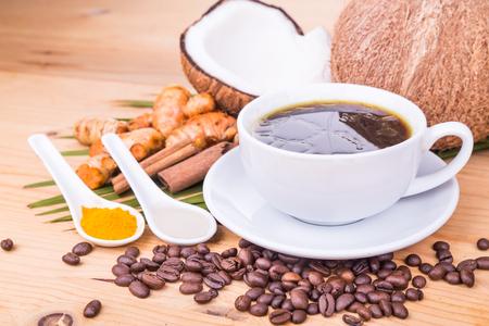 aceite de coco: Primer en el café mezclado con balas prensado en frío de aceite extra virgen de coco, la cúrcuma y el clavo en la mesa de madera, dieta cetogénica sana