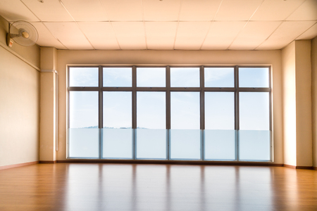 Perspective view of empty studio with wooden flooring illuminated with light from windows