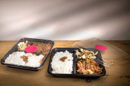 food tray: Two convenient take-away meal boxes with rice, meat and vegetable on wooden table top