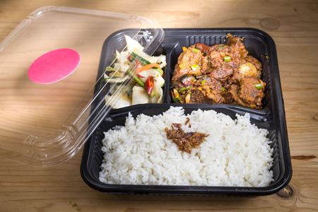 Convenient take-away meal box with rice, meat and vegetable on wooden table top
