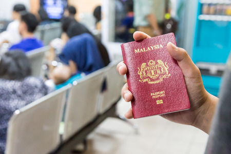 Person holding Malaysia international  passport against bokeh crowd background