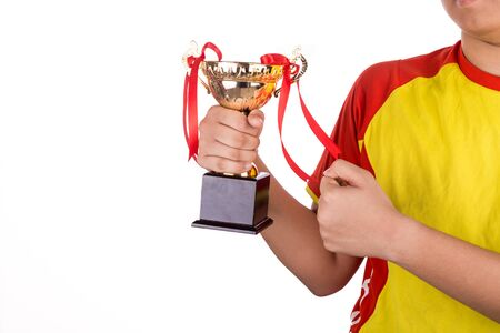 white achievement: Proud athlete gestures with firm fist whilst holding gold trophy, against white background Stock Photo