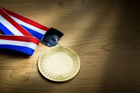 rendition: Generic sporting event gold medal with red and blue ribbon on wooden surface against ray of light.  Fine art rendition.