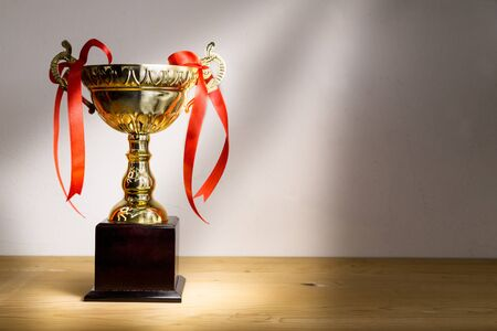rendition: Elegant gold trophy with red decorative ribbons on wooden table with ray of light.  Fine art rendition.
