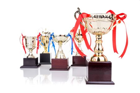 foreground focus: Group of elegant gold trophies with decorative ribbons, with focus on one on foreground Stock Photo