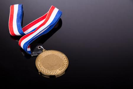 medaglia d'oro generico evento sportivo con il nastro rosso e blu su sfondo scuro