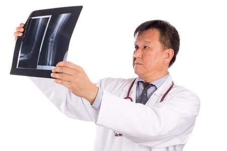 matured: Matured Asian orthopedic medical doctor examining X-ray film on white background