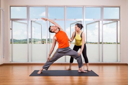 side angle pose: Yoga instructor guiding student perform extended side angle pose or Utthita Parsvakonasana in studio