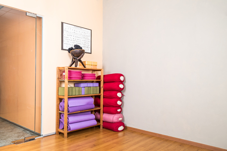 yoga pillows: Yoga blocks, pillow, mats, pads, accessories stacked in empty yoga studio with wooden flooring Stock Photo