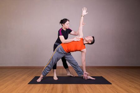 trikonasana: Series of yoga instructor guiding student perform triangle pose or Trikonasana in studio Stock Photo