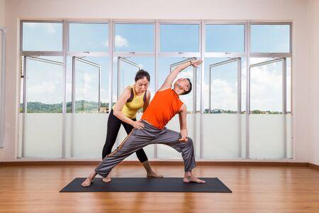 guiding: Yoga instructor guiding student perform extended side angle pose or Utthita Parsvakonasana in studio