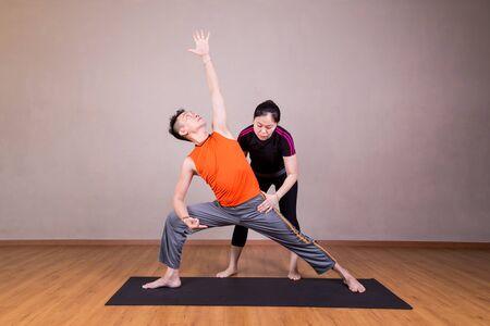 utthita: Yoga instructor guiding student perform extended side angle pose or Utthita Parsvakonasana in studio