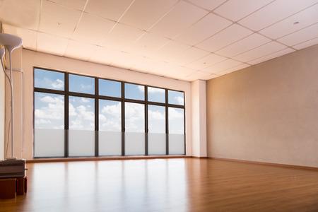 Lege yoga studio met houten vloeren, ramen met blauwe lucht en wolken