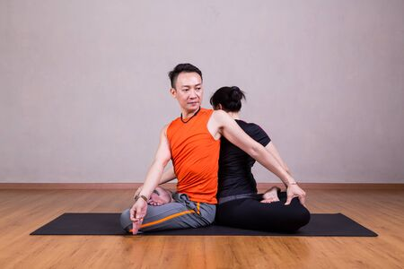 twist: Partner Twist Yoga Pose by a couple in studio