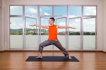 virabhadrasana: Yoga practitioner performing Warrior 2 or Virabhadrasana 2 pose in studio
