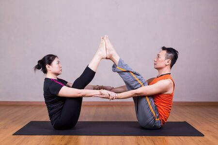 buddy: Partner Buddy Boat Yoga Pose by a couple in studio