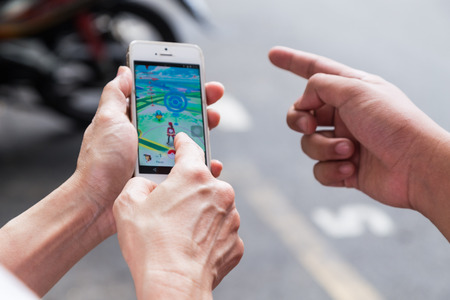 google play: KUALA LUMPUR, MALAYSIA, JULY 16, 2016: An IOS user plays Pokemon Go, a free-to-play augmented reality mobile game developed by Niantic for iOS and Android devices.