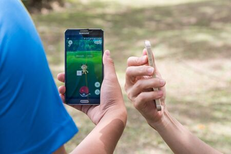 developed: KUALA LUMPUR, MALAYSIA, JULY 24, 2016: Two users play Pokemon Go, a free-to-play augmented reality mobile game developed by Niantic for iOS and Android devices.