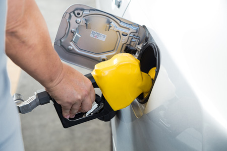 unleaded: Hand with nozzle fueling unleaded gasoline into car at station