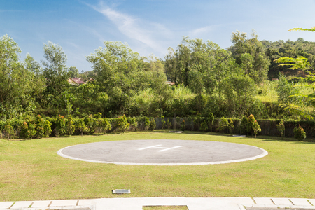 heliport: Helipad for helicopter landing within greenery setting