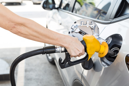 unleaded: Person holding yellow nozzle filling petrol into car at station Stock Photo