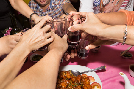 toasting wine: Group of Chinese toasting wine during meal celebration in restaurant