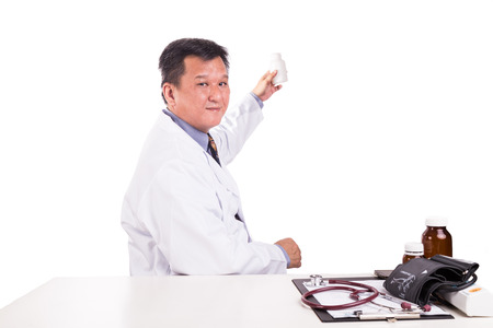 Matured Asian medical practitioner holding medicine seated behind desk on white background