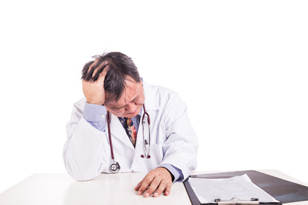 Depressed sad matured Asian doctor seated behind desk on white background