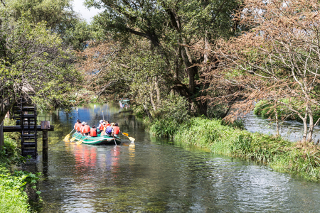 peddle: Group of people on raft peddling on serene scenic river in nature environment Stock Photo