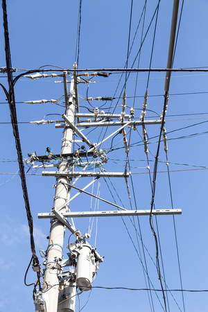 electricity pole: Electricity pole with wires grid against blue sky Stock Photo