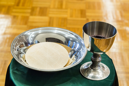 chalice: Catholic bread and wine in silver chalice during mass Stock Photo