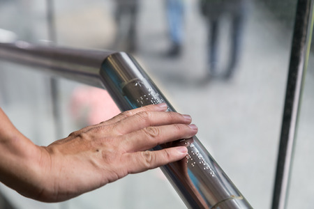Hand reading Braille inscriptions for the blind on public amenity railing 스톡 콘텐츠