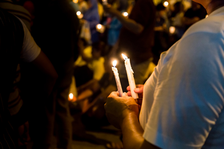 Group of people holding candle vigil in darkness seeking hope, worship, prayer Stock Photo