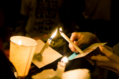 Group of people lighting candle vigil in darkness seeking hope, worship, prayer