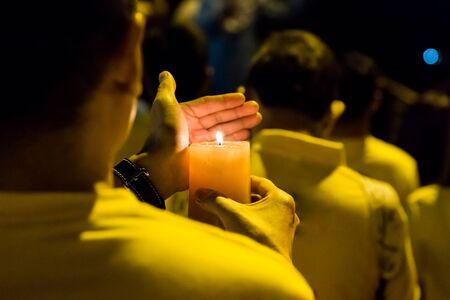 Group of people holding candle vigil in darkness seeking hope, worship, prayer Stock Photo