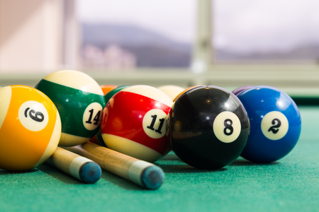 Closeup on snooker billards cue, chalk, balls on table with green surface