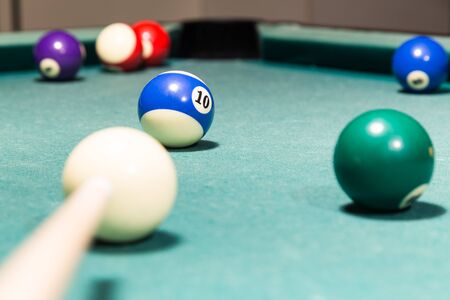 Cue aiming red ball into snooker pool billards table pocket Stock Photo
