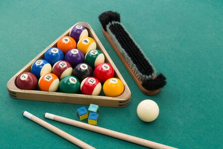 Snooker billards pool balls in triangle, chalk, cue, extender stick and brush on green table