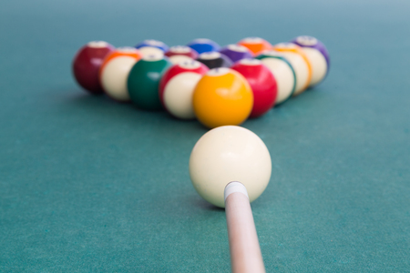 Focus on cue aiming white ball to break snooker billards on green table Stock Photo