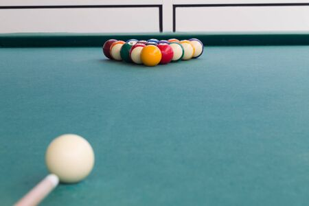 Cue aiming white ball to break snooker billards on green table