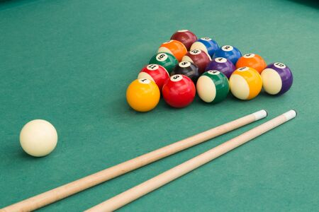 Snooker billards pool balls in triangle and cue stick on green table