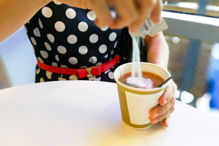 Hand pouring unhealthy non dairy creamer from sachet into hot coffee Stock Photo