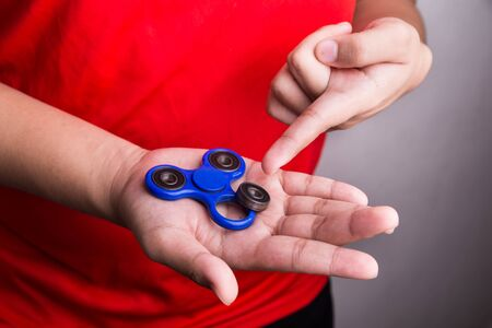 Person pointing dislodged weight from fidget spinner. Hazard and dangerous for child kids.